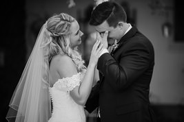 Bride and Groom seeing each other for the first time, Groom is hiding his eyes while he wipes away a tear and bride is gently touching his hand while smiling. The two are facing in towards each other. Black and white image.